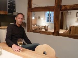 Wirt Peter Braun bei einem Glas Wein in der modernen Stube,